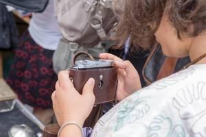 Frau schaut sich gebrauchte Kameras am Naschmarkt Flohmarkt an