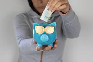 Frau schiebt einen Geldschein in die Urlaubskasse