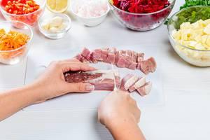 Frau schneidet Schweinefleisch auf einem Küchentisch