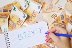 """Frau schreiben """"Brexit"""" auf einen Zettel zwischen 50-Euro-Geldscheinen"""