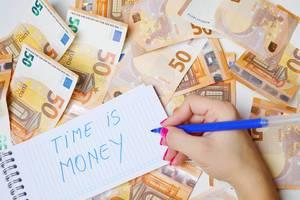 """Frau schreiben """"Time is Money / Zeit ist Geld"""" auf einen Zettel zwischen 50-Euro-Geldscheinen"""