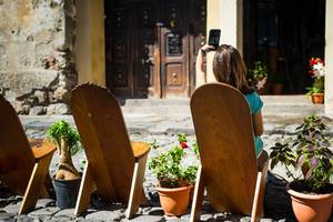 Frau sitzt auf interessant geformten Holzstühlen vor Fassade und macht Selfie