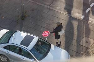 Frau verteilt Stop Klimakrise - Stop GroKo Schilder an Auto Fahrer