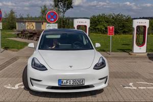 """Frau wartet im weißen Elektroauto """"Tesla Model 3"""", während der Batterieaufladung an der Supercharger-Ladestation am Rasthof in Wilnsdorf"""