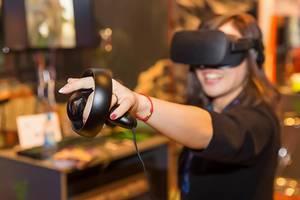 Frau zeigt Ganzkörpereinsatz beim Gaming mit der VR-Brille