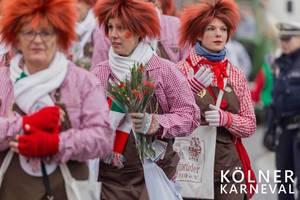 Frauen in Clownskostum verteilen Blumen aus Stofftaschen der Fidelen Zunftbrüder 1919 e.V. beim Kölner Karneval