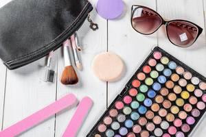 Frauen-Kosmetik auf einem weißen Holztisch - Sonnenbrille, Schminkpallete, Pinsel und Make-Up-Pads