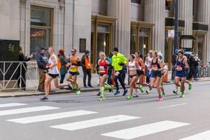 Frauen und Männer nehmen am Chicago Marathon in den USA teil und laufen am Central Standard Building vorbei