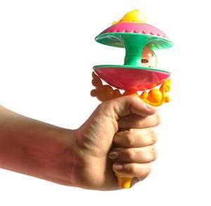 Frauenhand hält bunte Baby-Spielzeugrassel für Neugeborene in der Hand, isoliert vor weiß