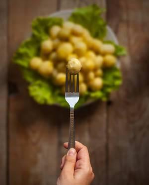 Frauenhand hält eine geschälte Babykartoffel auf einer Gabel aufgespießt, vor unscharfem Hintergrund mit einem Teller auf einem Holztisch