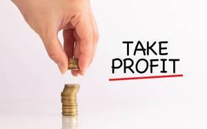 """Frauenhand hebt Münzen auf, neben dem Text """"Take Profit""""  (Gewinn erzielen)"""