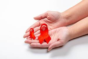 Frauenhände zeigen zwei Bänder als Symbol für den Kampf gegen Brustkrebs
