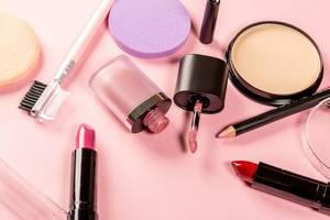 Frauenkosmetik wie Puder, Lippenstift, Lipgloss, Lipliner und Brauenbürste vor rosa Hintergrund