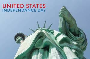 Freiheitsstatue aus der Froschperspektive vor blauem Himmel, neben dem Text United States Independence Day