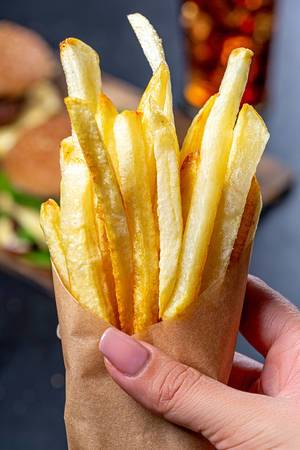 French fries in a paper wrapper in a woman
