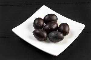 Fresh Black Olives on a White Square Plate on Dark Background