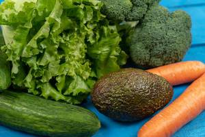 Fresh Carrots, Avocado, Broccoli, Lettuce and Cucumber on the blue boards (Flip 2020)