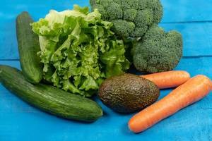 Fresh Carrots, Avocado, Broccoli, Lettuce and Cucumber on the wooden table (Flip 2020)
