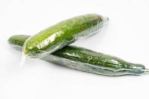 Fresh Cucumber in the plastic wrap above white background (Flip 2020)