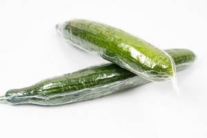 Fresh Cucumber in the plastic wrap above white background