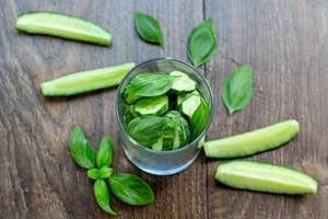 Fresh cucumber slices and Basil leaves on wooden background. The concept of detox cocktail ingredients