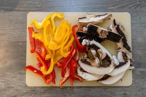 Fresh cut mushrooms with yellow and red pepper slices on a cutting boar - top view