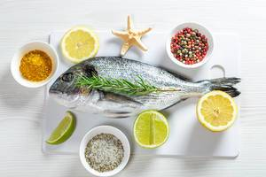 Fresh Dorada with lime, lemon, spices and starfish. Top view (Flip 2019)
