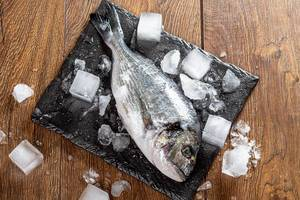 Fresh Dorado fish with ice cubes on wooden table (Flip 2019)