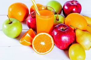 Fresh fruit: Oranges, apples, pears, lemon, pomegranate and fruit juice in a glass on white wooden background