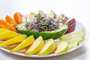 Fresh fruit slicing on a white plate with avocado and micro green cabbage (Flip 2019)
