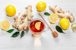 Fresh ginger roots, lemons and green leaves with a Cup of tea on a white wooden background
