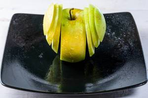 Fresh green Apple sliced on a plate