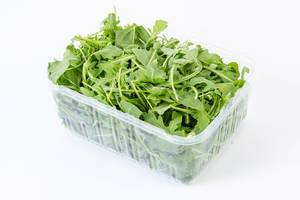 Fresh Healthy Green Rucola in the box above white background (Flip 2019)