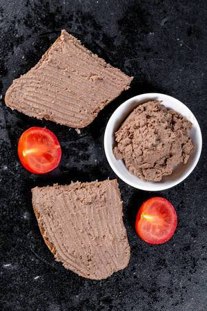 Fresh homemade chicken liver pate on bread over black background