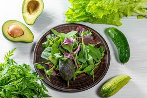Fresh leaves assorted lettuce, spinach, arugula with avocado and cucumbers. Ingredients for a healthy diet
