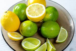 Fresh lemons and limes whole and pieces on a glass black plate
