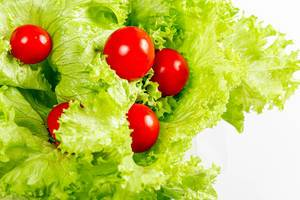 Fresh lettuce with cherry tomatoes on white background
