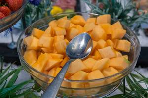 Fresh mango cut in pieces, in a glass bowl with spoon, at the fruit buffet