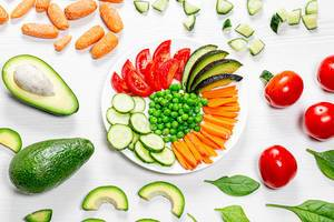 Fresh multicolored sliced vegetables on and around the plate. Top view