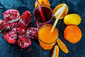 Fresh pomegranate and orange juice with ripe fruit