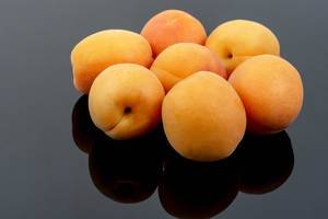 Fresh raw Apricots on the black background