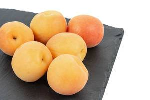 Fresh raw Apricots on the black stone tray background (Flip 2019)
