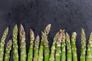 Fresh raw green asparagus on black background (Flip 2019)