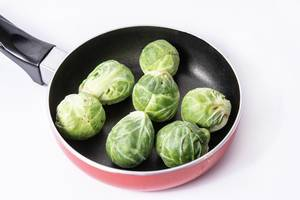 Fresh raw healthy Brussel Sprouts in the frying pan (Flip 2019)