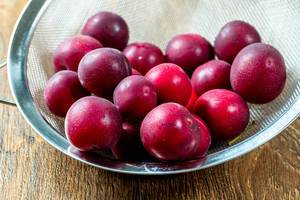 Fresh red plums in a sieve