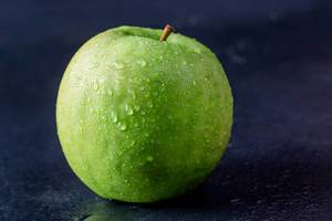 Fresh ripe apple on black background. Food ingredients. Health product