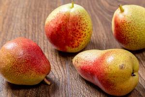 Fresh ripe pears on brown wooden background