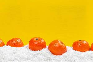 Fresh ripe tangerines on snow with yellow background behind with free space (Flip 2019)