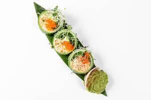 Fresh rolls with cucumber, avocado, crab, arugula and micro-greens on a large green leaf. Top view (Flip 2019)