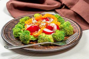Fresh salad of broccoli, radish, bell pepper and flax seeds, sesame seeds, poppy seeds